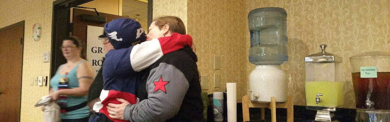 Two women, one in a Captain America hoodie, one in a Winter Soldier hoodie, kissing.